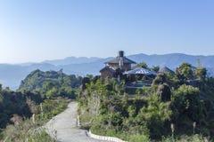 Hus och väg på en grön kulle mot den blåa himlen och konturerna av berg i en dimmig dal royaltyfria bilder