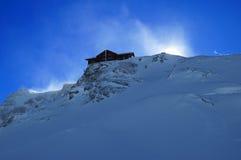 Hus på överkanten av ett snöig berg Arkivfoton