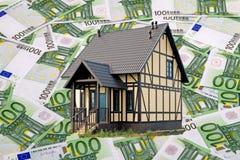 Hus på bakgrunden av sedlarna av 100 euro Royaltyfri Fotografi
