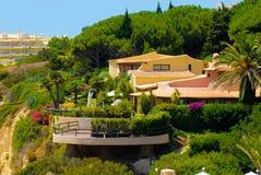Hus på en överkant av en klippa, frodiga Front Garden, Europa ferier royaltyfri fotografi