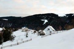 Hus på en backe som täckas med snö- och gräsplanträd på siden Royaltyfri Foto