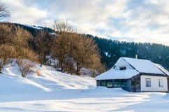 Hus på en backe som täckas med snö- och gräsplanträd på siden Arkivbilder