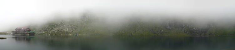 Hus på en dimmig berglake Fotografering för Bildbyråer