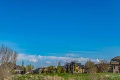 Hus på ett rikt grönt fält med träd och bruna gräs i förgrunden arkivbild