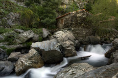 Hus på floden med små vattenfall Arkivfoto