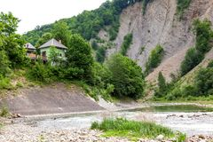 Hus på floden nära berget Fotografering för Bildbyråer