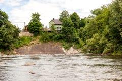 Hus på floden nära berget Arkivbild