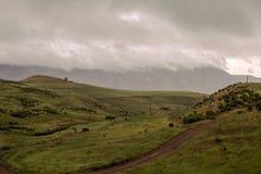 Hus på kullen i berg och slingrig bergväg Arkivfoto