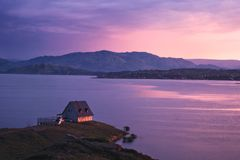 Hus på kusten av sjön på solnedgången Royaltyfria Bilder