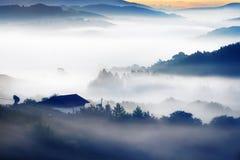 Hus på morgon med dimmiga berg arkivfoton