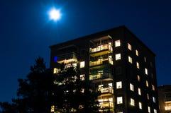 Hus på natten med månen som över skiner Royaltyfri Fotografi