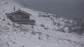 Hus på Rocky Shore av fjorden och snöfallet långsam rörelse kretsat lager videofilmer
