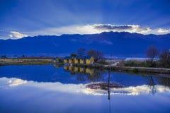 Hus reflekterat i sjön nära berget Arkivfoto
