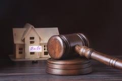 Hus som är till salu, auktionhammare, symbol av myndighet och miniatyrhus Rättssalbegrepp Royaltyfri Foto