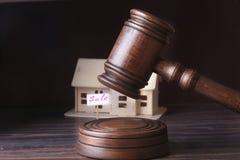 Hus som är till salu, auktionhammare, symbol av myndighet och miniatyrhus Rättssalbegrepp Royaltyfri Fotografi