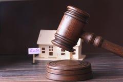 Hus som är till salu, auktionhammare, symbol av myndighet och miniatyrhus Rättssalbegrepp Royaltyfria Bilder