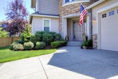 Hus som är yttre med körbanan och amerikanska flaggan. Arkivbilder