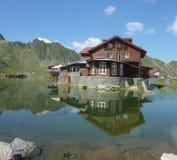 Hus som avspeglar i sjön Royaltyfria Bilder