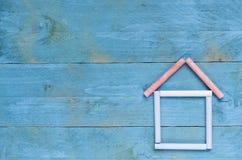 Hus som göras av krita på blå träbakgrund Söt hem- concep Royaltyfri Bild