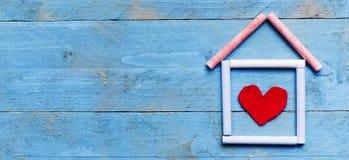 Hus som göras av krita på blå träbakgrund Söt hem- concep Fotografering för Bildbyråer