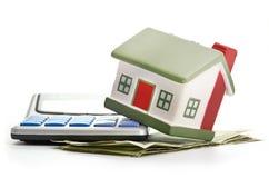 Hus som sitter med en räknemaskin och en dollar Arkivfoton