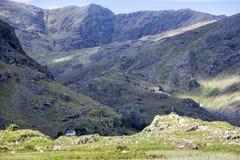 Hus som ställa i skuggan av berg Arkivfoto