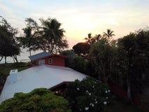 Hus, träd och strand för soluppgång flyg- rött i Waimanalo Royaltyfri Bild
