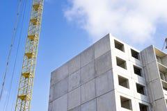 Hus under konstruktion och fragmentet av konstruktionskranen Arkivbild