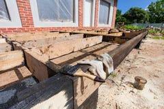 Hus under under-renovering, omdana och konstruktion borsten för att måla svart koltjära eller bitumen Fotografering för Bildbyråer