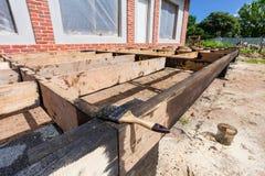 Hus under under-renovering, omdana och konstruktion borsten för att måla svart koltjära eller bitumen Arkivfoton