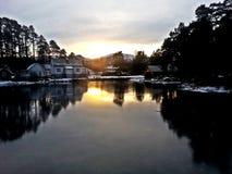 Hus vid den djupfrysta sjön Arkivfoto