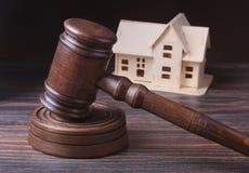 Husauktion, auktionhammare, symbol av myndighet och miniatyrhus Rättssalbegrepp Arkivfoto