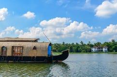 Husbåt i avkrokar av Kerala mot en blå himmel och en solit Royaltyfri Foto