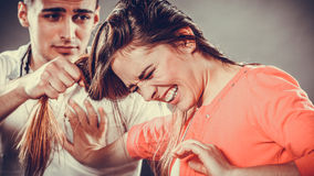 Husband abusing wife pulling her hair. Violence. Stock Photo