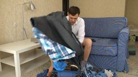 Husband alcoholic sits on the couch gets out of a suitcase alcohol. a divorce. Fhd stock footage