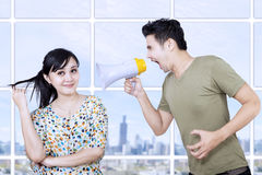Husband angry at wife using megaphone. In their apartment with cityscape Stock Image