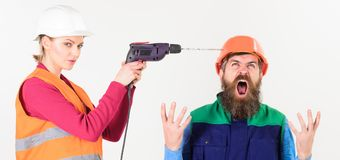 Husband annoyed by wife. Builder makes hole in male head. Marriage issues concept. Woman drills head of man, white background. Man in helmet with shouting face royalty free stock photo