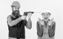 Husband annoying his wife. Man with happy face drills. Head of woman, white background. Builder, repairman makes hole in female head. Woman on scared face in royalty free stock photography