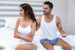 Husband arguing with wife while sitting on bed Royalty Free Stock Images