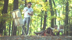 Husband artist drawing picture on autumn nature. Happy Autumn Family. stock video footage