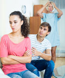 Husband asking wife for forgiveness after argue indoors. Young men comforting girl after domestic conflict with mother royalty free stock photo