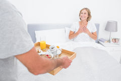Husband bringing breakfast in bed to delighted wife. In bedroom at home Stock Photos