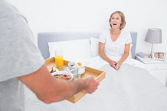 Husband bringing breakfast in bed to surprised wife. In bedroom at home Royalty Free Stock Photography