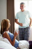 Husband Chatting With Wife Over Drink In Bed Royalty Free Stock Image