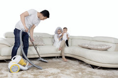 Husband cleaning carpet with vacuum cleaner Royalty Free Stock Photo