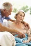 Husband Comforting Senior Woman Feeling Unwell Resting Under Blanket Stock Image