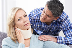 Husband Comforting Wife Suffering With Neck Injury Stock Photos