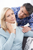 Husband Comforting Wife Suffering With Neck Injury Stock Image