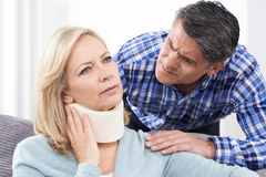 Husband Comforting Wife Suffering With Neck Injury Royalty Free Stock Images