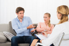 Husband Complaining To Psychologist. Husband And Wife Sitting On Couch Complaining To Psychologist stock images